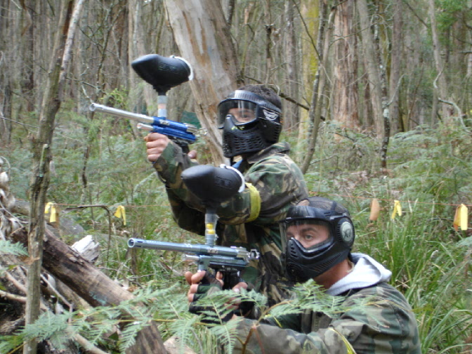 Two paintball players hiding behind a tree aiming at their targets.