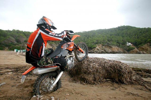 A rider balanced on a log with his bike.