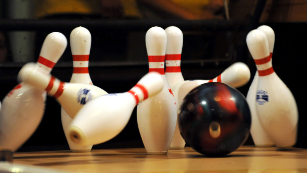 A bowling ball strikes the pins