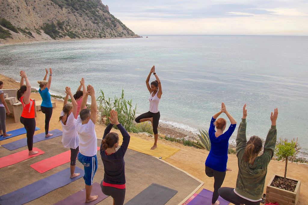 People taking part in a yoga class next to the beach