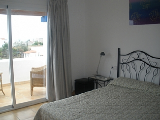 Room with a balcony and a double bed in a rental house of Ibiza