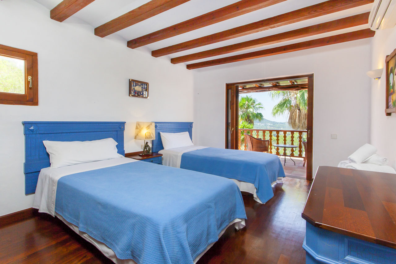 Room with two single beds and access to the terrace overlooking the landscape
