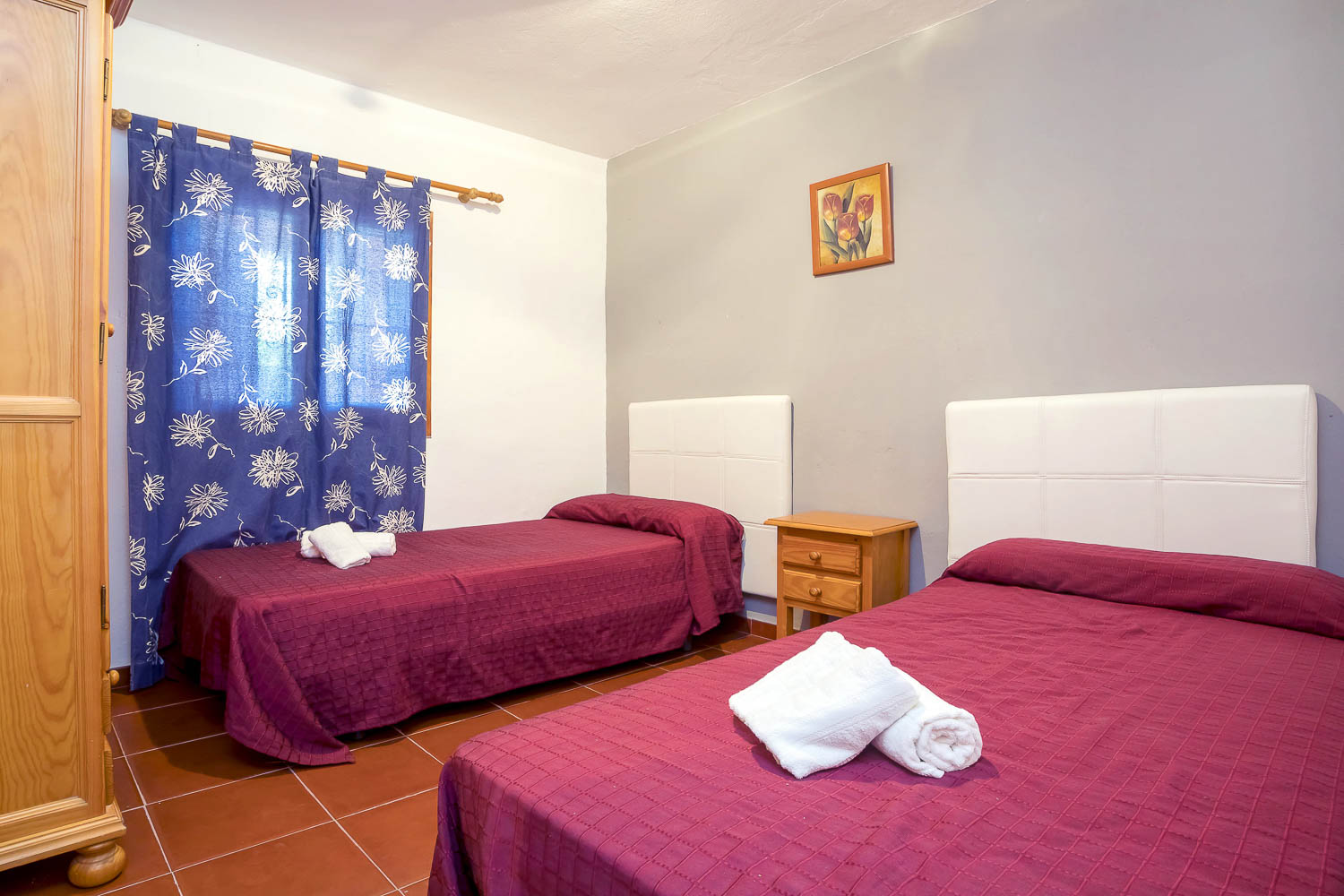 Double and a single bed in a room of a rental house in Ibiza