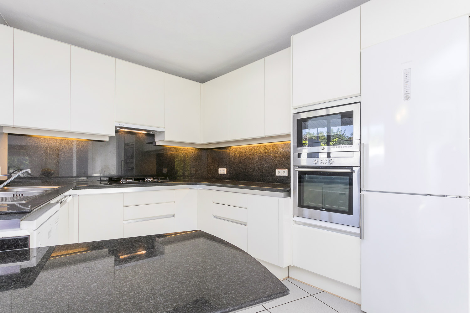 Modern fully equipped kitchen with central island in Ibiza rental house
