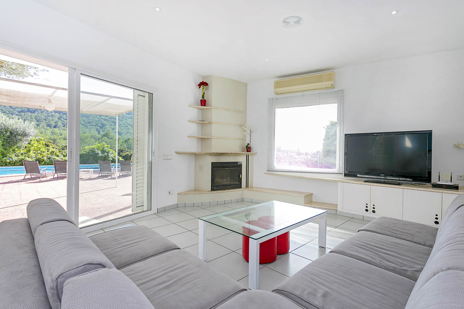 Bright and spacious living and television area with views to the countryside and direct access to the pool and garden
