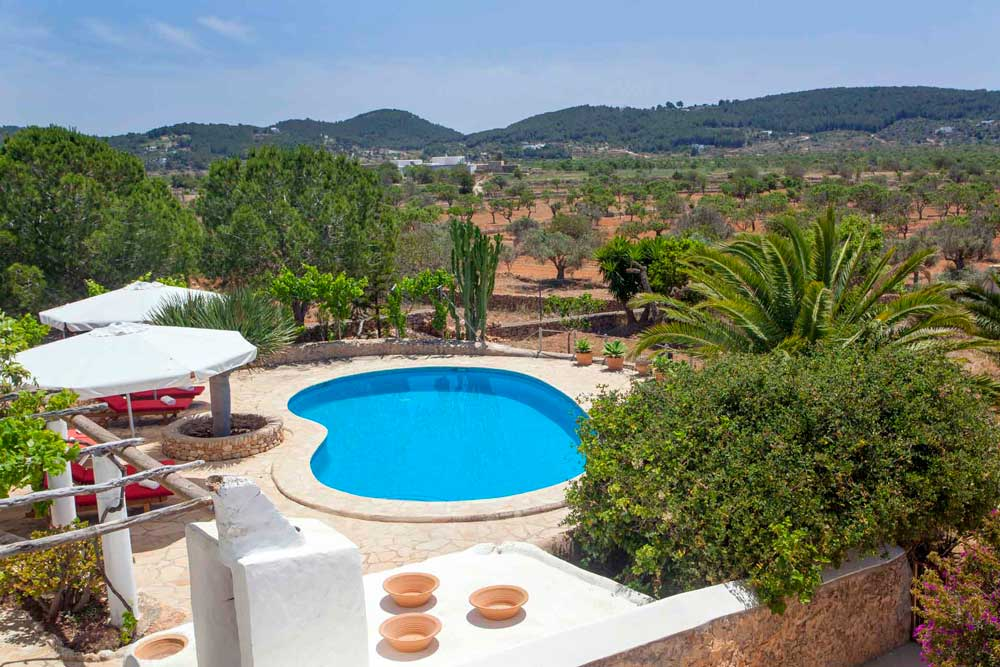 general view of the pool zone and the garden from a rental house in ibiza