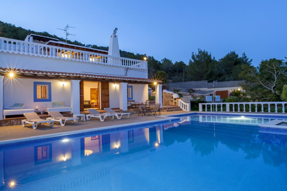 Exterior of house rental at night pool and lighted outdoor areas